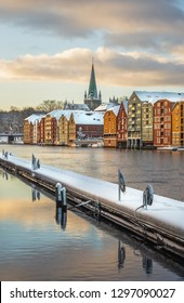 Trondheim, Sor-Trondelag / Norway - 01 23 2019: Old houses and magazines by Nidelva river in Trondheim, Nidarosdomen Cathedral in back. Beautiful winter time in Norway.