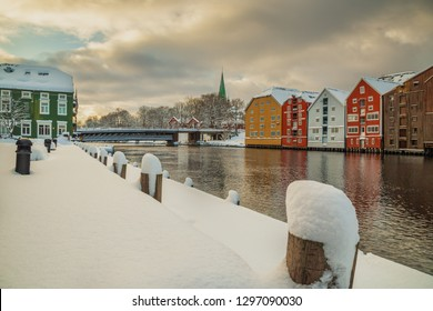 Trondheim, Sor-Trondelag / Norway - 01 23 2019: Old wooden buildings, magazines, by the shores of Nidelva river, winter time in Trondheim, Norway.