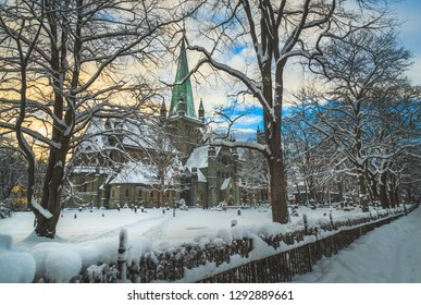Trondheim/Norway - January 21st 2019:Nidarosdomen Cathedral by Nidelva river in Trondheim. Beautiful wintertime. Most famous gothic, norwegian church. Park and graveyard around the cathedral.
