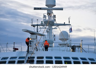 Trondheim/Norway-12-03-2018: Two men ajusting the navigational equipment on top of a ship that is moored in the harbour of Trondheim