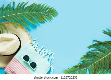 Tropacal vacation. Straw beach sunhat, sun glasses, beach towel leaf of fern on pastel blue background. Top view with copy space. Summer.
