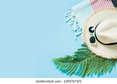 Tropacal vacation. Straw beach sunhat, sun glasses, beach towel, leaf of fern on blue. Top view with copy space. Minimal summer.