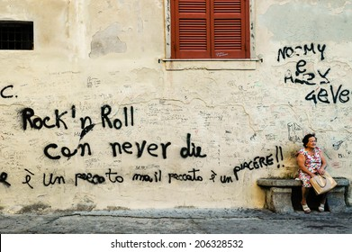 "TROPEA, CALABRIA, ITALY, April 2014: Graffiti in an old Italian town in Calabria. Old woman sitting next to a wall with the words ""Rock'n roll can never die"""