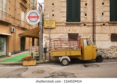 Tropea, Calabria / Italy - June 2018: Man waiting in his small yellow truck