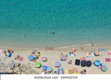 Tropea, Calabria/ Italy - June 25 2016: People relaxing on the beach, near turquoise seawater, captured from above. Bird perspective.