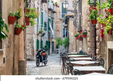 Tropea, ITALY - JUNE 27, 2017: Old Buildings,motorbike, outdoor restaurant on narrow street in typical Italian City town Tropea, Calabria