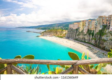 Tropea town and Tyrrhenian Sea beach, colorful buildings on top of high big rocks, view from Sanctuary church of Santa Maria dell Isola with fence foreground, Vibo Valentia, Calabria, Southern Italy