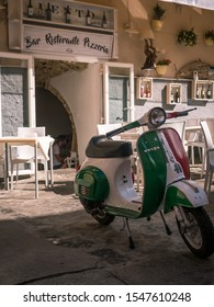 Tropea/Italy - 10/05/2019: Vespa motorbike in colors of Italian flag infront of traditional restaurant and pizzaria with lettering in Tropea, Calabria, Italy