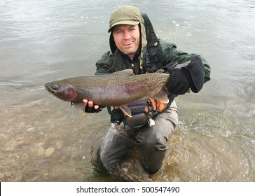 Trophy fish - a fly fisherman holding a huge trophy Rainbow Trout, a fish related to salmon (salmonid)