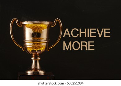 trophy in front of blackboard with text achieve more