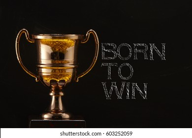 trophy in front of blackboard with text born to win