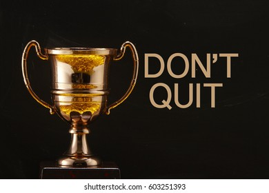 trophy in front of blackboard with text don't quit