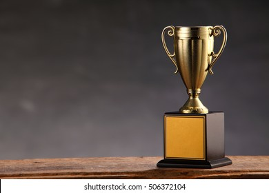 trophy on top of old wooden table in front of blackboard