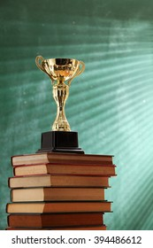 trophy on top stack of book in front of black board
