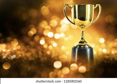 trophy over wooden table and dark background bokeh.
