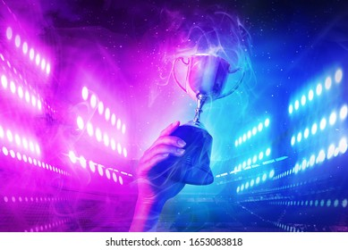 Trophy with smoke effect holding on hand and background blue and violet light for e-sport winner event.