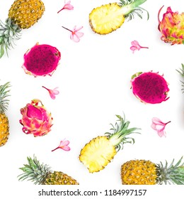 Tropic frame of pineapple and dragon fruits with tropical pink flowers on white background. Flat lay, top view.
