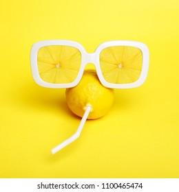 Tropic Lemon in vintage sunglasses with lemon slices reflection. Minimal fashion summer mood concept. Trendy monochrome yellow.