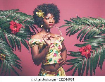 Tropical Afro American Pin-up Holding Sunglasses. Against Pink Background.