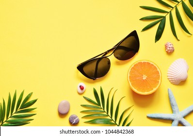 Tropical Background. Palm Trees Branches with starfish and seashell on yellow background. Travel. Copy space
