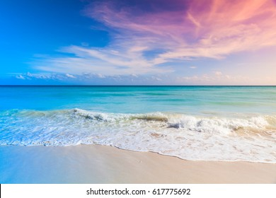 Tropical beach background, white sand and azure shore water under cloudy blue sky. Caribbean Sea coast, Dominican republic, Saona island. Tonal correction, colorful gradient filter effect