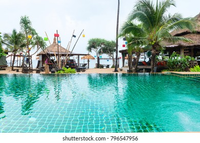 Tropical beach bars and restaurant with big clear swimming pool, green palms and blue sea on background