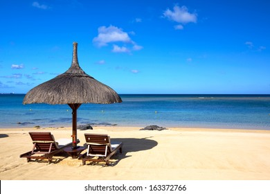 Tropical beach with chairs and umbrella in Mauritius