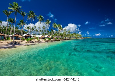 Tropical beach with with coconut palm trees and villas on Samoa Island