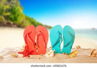 Tropical beach with colored flip flops, summer holiday background. Travel and beach vacation, free space for text.