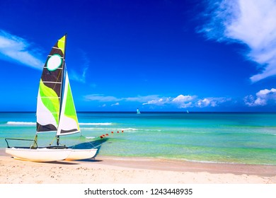 Tropical beach with a colorful sailboat on a summer day with turquoise water and blue sky. Varadero resort, Cuba.