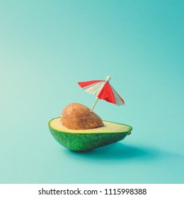 Tropical beach concept made of avocado fruit and sun umbrella. Creative minimal summer idea.