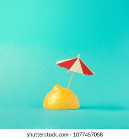 Tropical beach concept made of lemon and sun umbrella. Creative minimal summer idea.
