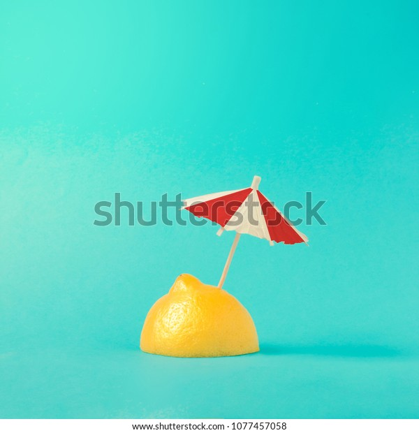 Tropical beach concept made of lemon and sun umbrella. Creative minimal summer idea.