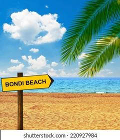 Tropical beach and direction board saying BONDI BEACH