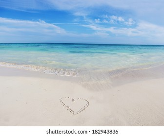 Tropical beach and heart drawing on the sand