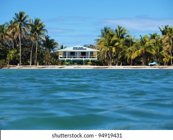 Tropical beach house with solar panels viewed from the Caribbean sea
