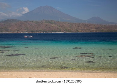 tropical beach landscape with clear blue sea and sky, sea channel between java en Bali, view at vulcano Gunung Raung,