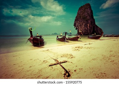 Tropical beach landscape in vintage style. Thai traditional long tail boats at ocean gulf under cloudy sky. Pranang cave beach, Railay, Krabi,Thailand