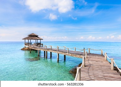 Tropical beach landscape with a wooden pier or jetty with hut above transparent turquoise clear sea water and blue sunny sky, beautiful vacation destination