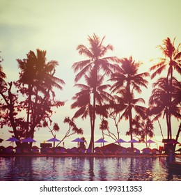 Tropical beach with palm trees and water reflections. Vintage instagram effect. Square composition.