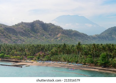 Tropical beach with palms and boats and big volcano on background on Bali in Candidasa, Indonesia