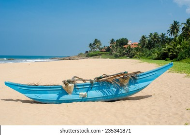 Tropical beach with palms and fishing boats in Sri-Lanka