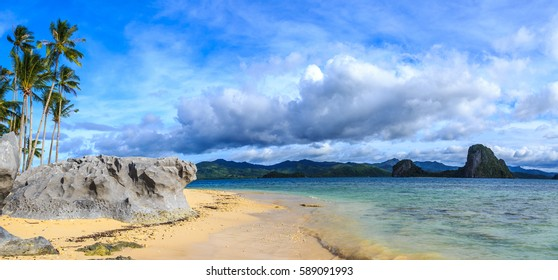 Tropical beach panorama with blue sky, clouds, rocks and palm trees, Palawan, Philippines