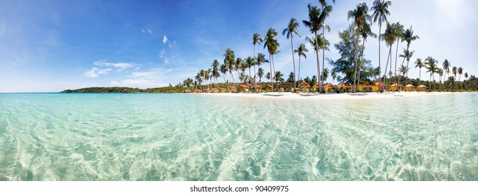 Tropical beach panorama with palm trees on small island