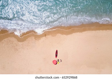 Tropical beach with red umbrella and surfboard - Top down aerial view