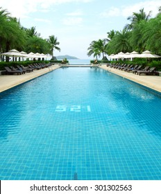 Tropical beach resort hotel swimming pool -- tropical beach vacation and travel concept.