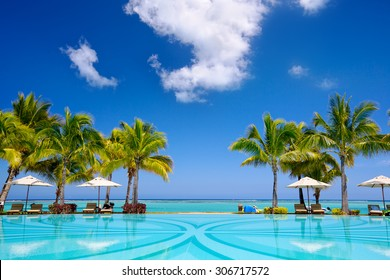 Tropical beach resort with  lounge chairs and umbrellas, Mauritius - Shutterstock ID 306717572