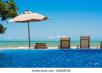Tropical beach resort with lounge chairs and umbrella, Cha-am - Hua Hin, Thailand