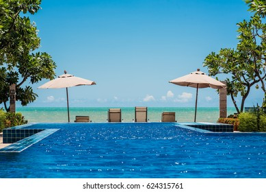 Tropical beach resort with lounge chairs and umbrella with the sea and blue sky background, Cha-am - Hua Hin, Thailand