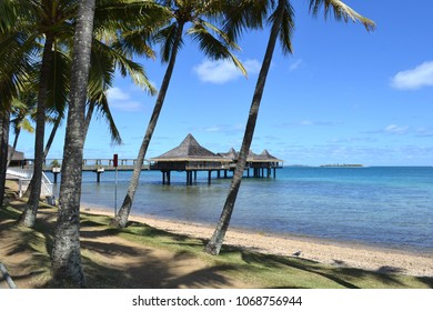 Tropical beach scene with native style building on jetty, Anse Vata Bay, New Caledonia